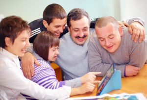 33677207 - group of happy people with disability having fun with tablet