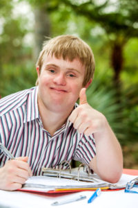 35502540 - close up portrait of handicapped student doing thumbs up at desk outdoors.